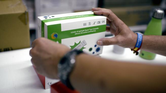 Una farmacéutica coloca una de las cajas de un test de antígeno para Covid-19.