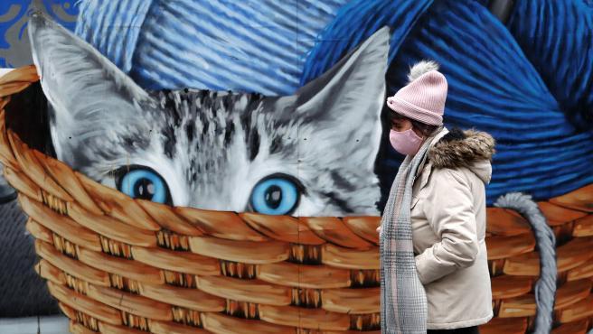 Una mujer con mascarilla junto a un mural con un gato en Glasgow