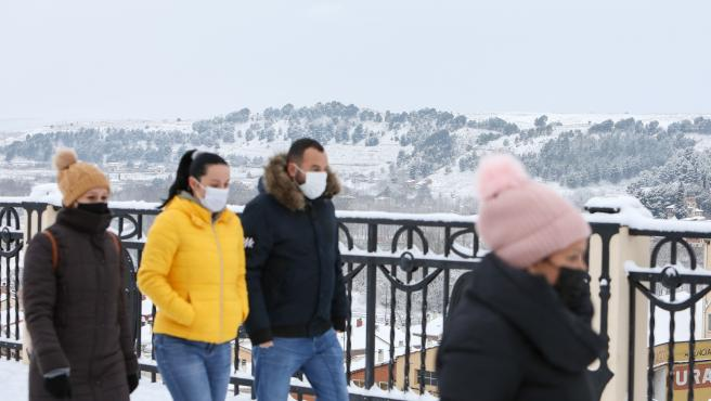 Varias personas caminan durante la nevada en Teruel.