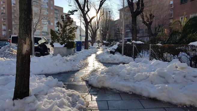 Calle del barrio de Moratalaz (Madrid), con un pasillo entre la nieve, una semana después de la nevada que trajo el temporal Filomena.