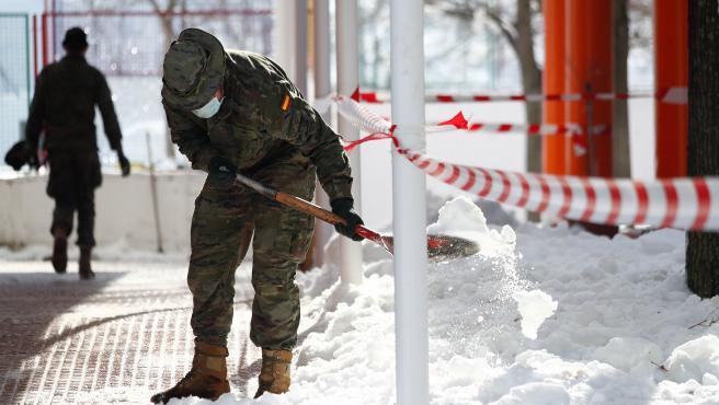 Un militar de la Unidad Militar de Emergencias (UME) colabora en la retirada de nieve y hielo en Valdemoro.