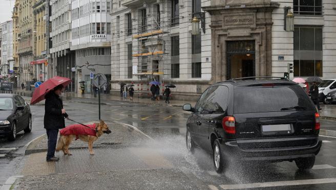 A Coruña Temporal de lluvia y viento Un coche salpica a un hombre con su perro en el Obelisco 20/01/2021 Foto: M. Dylan / Europa Press
