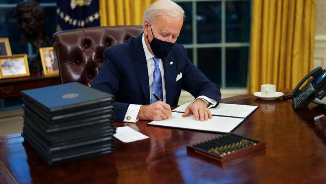 El presidente de EE UU, Joe Biden, firma sus primeras órdenes ejecutivas en el Despacho Oval de la Casa Blanca.