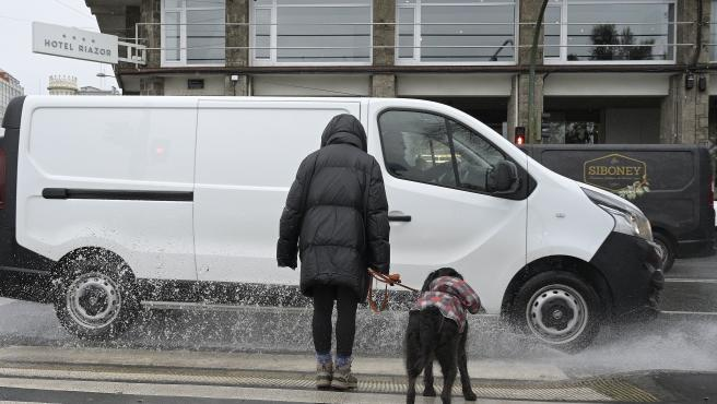 A Coruña Temporal de lluvia y viento Una furgoneta salpica a una mujer con su perro en el paseo Marítimo 20/01/2021 Foto: M. Dylan / Europa Press