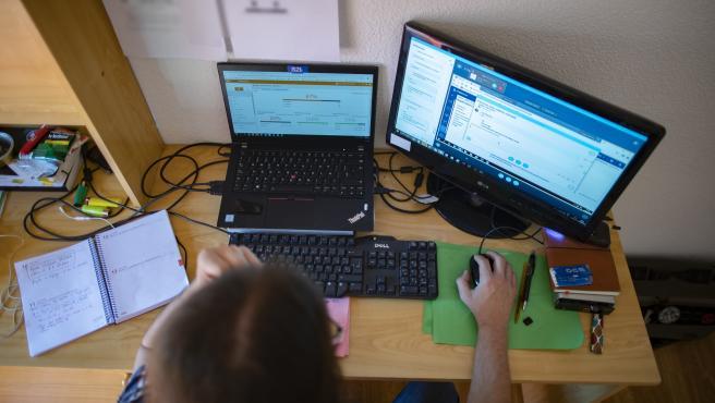 Imagen de archivo de una persona teletrabajando desde su casa con un portátil.