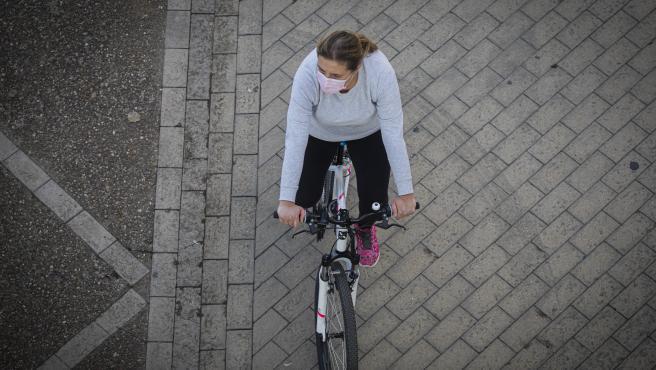 Una mujer con mascarilla montando en bicileta.