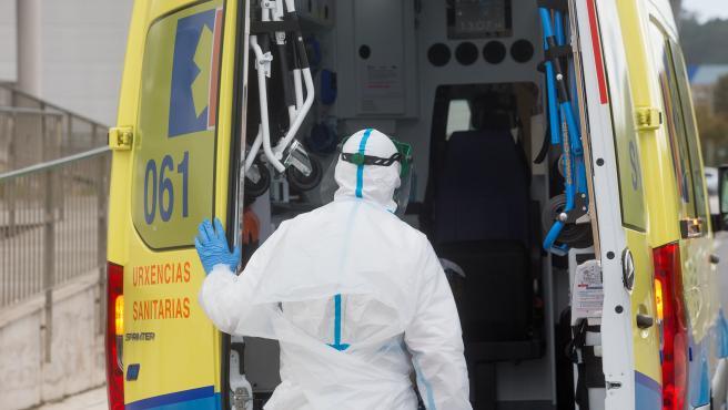 Un trabajador sanitario totalmente protegido cierra la puerta de una ambulancia.