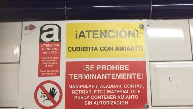 Cartel de Metro alertando de presencia de amianto en el pasillo de la línea 10 de la estación de Tribunal.