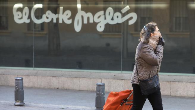 Una mujer con un carro de la compra camina junto a uno de los centros de El Corte Inglés en Madrid.