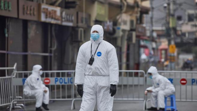Personal de seguridad vigila una zona de Shanghái, China, puesta en confinamiento tras detectarse un brote de COVID-19.