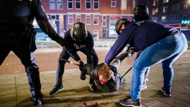 Un hombre es arrestado por la policía durante los disturbios en Rotterdam.