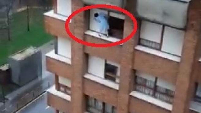 Una mujer limpia las persianas subida al alféizar de una ventana de un séptimo piso.