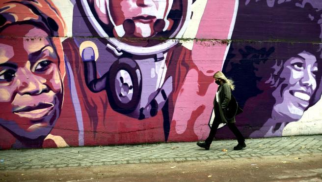 Una mujer pasa por el mural feminista en el polideportivo municipal de la Concepción en el distrito de Ciudad Lineal