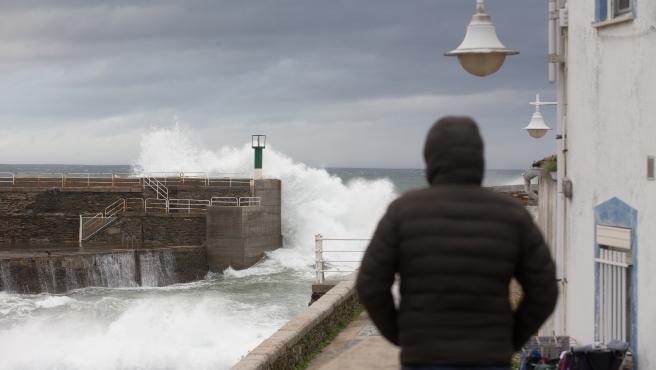 Ribadeo, Lugo. La borrasca Bella entra en la Peninsula dejando a su paso temporal en el mar, fuertes vientos y descenso de las temperaturas. En la imagen, un hombre observa el temporal en el Puerto de Rinlo en la tarde del domingo 27 de Dic
