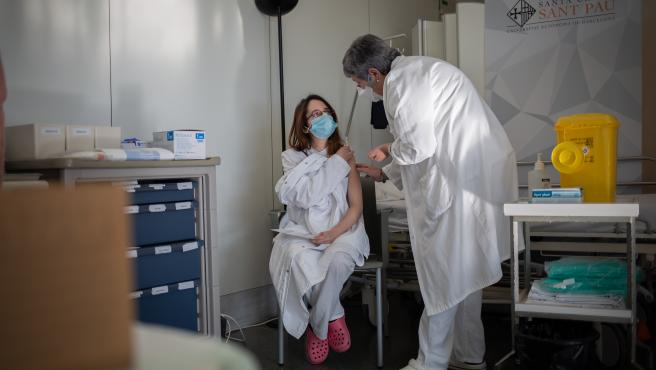 Una enfermera vacuna a un profesional sanitario con la vacuna de Pfizer-BioNtech contra el COVID-19 en el Hospital de la Santa Creu i Sant Pau de Barcelona, Catalunya (España), a 14 de enero de 2021.