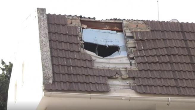 Un tejado destrozado a causa de la caída de una una palmera.