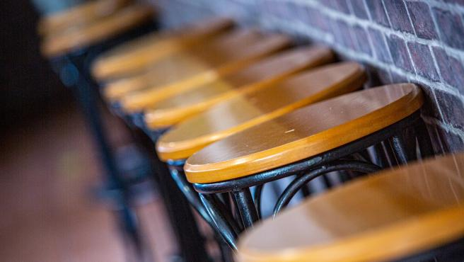 Taburetes vacíos en la barra de un bar.