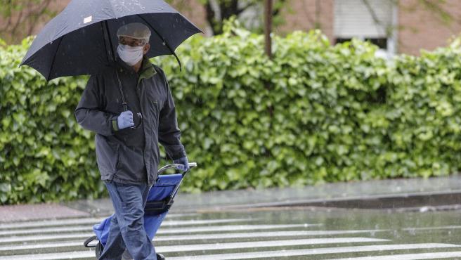 Transeúntes protegidos con mascarilla y un paraguas caminan por las calles de la capital un día marcado por la llegada a la península de una borrasca fría que ha activado la alerta por viento o lluvia en 8 comunidades, entre ellas, Madr