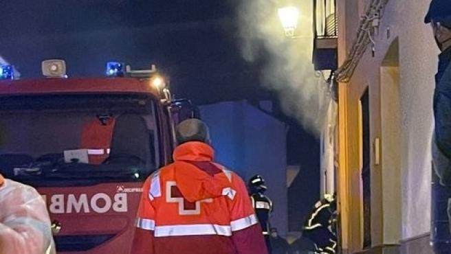 Un bombero entra en la vivienda en llamas.