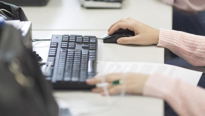 Una mujer trabajando con un ordenador.