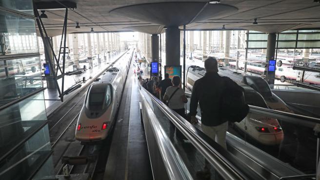 Varios pasajeros acceden al andén por una cinta mecánica en la estación Madrid-Puerta de Atocha durante el viernes previo al primer fin de semana tras el estado de alarma, en Madrid (España), a 26 de junio de 2020.