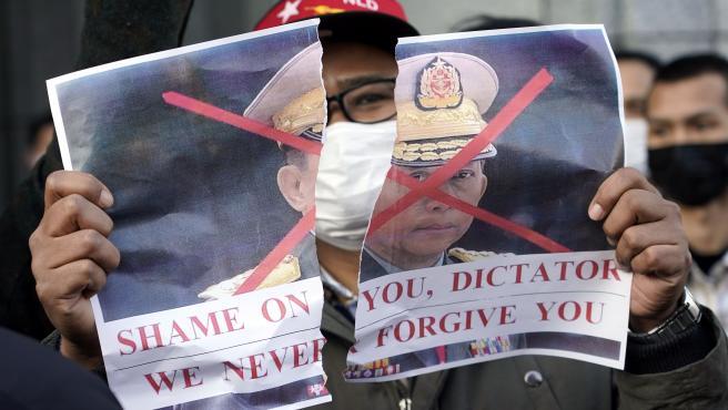 Un miembro de la comunidad birnana en Japón sostiene una foto rota del jefe militar de Birmania, Min Aung Hlaing, durante una protesta frente a la sede de la ONU en Tokio.
