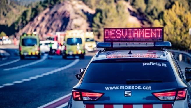 Un coche de Mossos d'Esquadra y ambulancias del Sistema d'Emergències Mèdiques (SEM) durante un accidente de tráfico en una imagen de archivo.