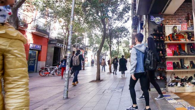 Un joven sale de una tienda de la céntrica calle de Fuencarral, en Madrid (España).
