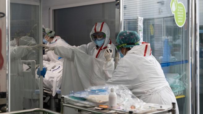 Una sanitaria se coloca una bata para entrar al box de un paciente con Covid-19 en la UCI del Hospital del Mar (Barcelona).