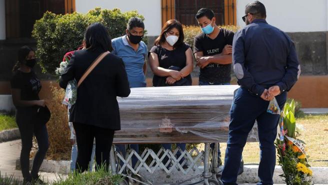 Familiares de una persona fallecida pro COVID-19, durante el funeral, en Guadalajara, Jalisco (México).