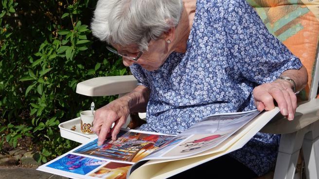 Una anciana observa un álbum de fotos, en una imagen de archivo.