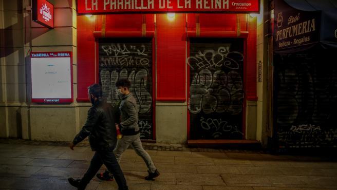 Dos jóvenes pasan por delante de un restaurante cerrado durante el primer día del toque de queda a las 10 de la noche, en Madrid (España), a 25 de enero de 2021.