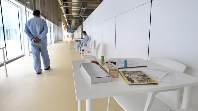 Un paciente del Zendal pasea junto a una zona de juegos de mesa mientras otro lee un libro.