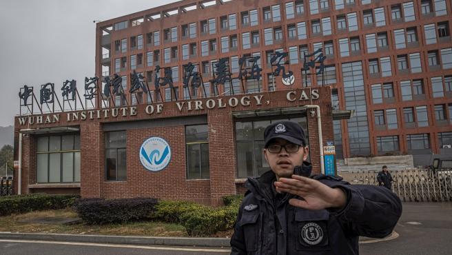 Un miembro del equipo de seguridad intenta evitar que se tomen fotografás del Instituto de Virología de Wuhan, en China.