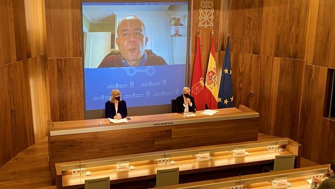 La consejera Ollo y el director general, Martín Zabalza, con el director del informe, Javier Dorado en pantalla, durante la comparecencia de prensa
