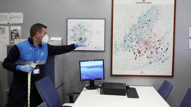 Un trabajador del Canal de Isabel II junto al mapa de los puntos en los que se toman muestras de agua en busca de la Covid-19.