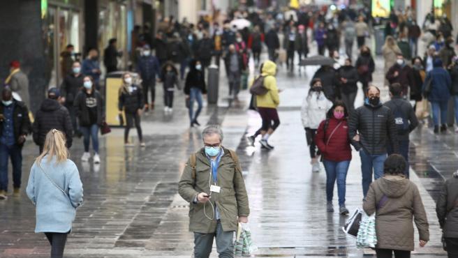 Gente pasea por la calle con mascarillas en Madrid.