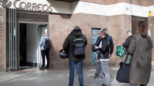 Varias personas hacen cola en una oficina de Correos de Barcelona.