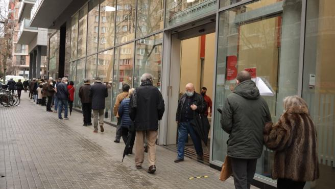Un hombre sale por la puerta establecida de salida tras ejercer su derecho al voto, mientras otros hacen cola para votar en un colegio electoral de Barcelona.