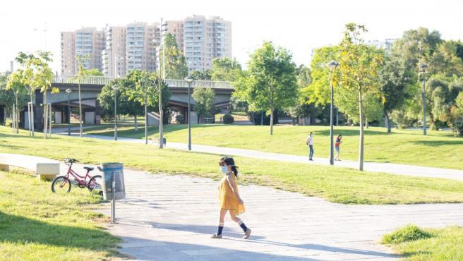 Una niña pasea por una zona verde de Valencia.