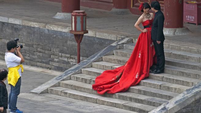 Una pareja de novios durante una sesión fotográfica en el Templo del Cielo, en Pekín, China.