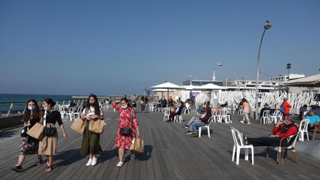 Personas con mascarillas por el coronavirus, en el paseo marítimo de Tel Aviv, Israel.