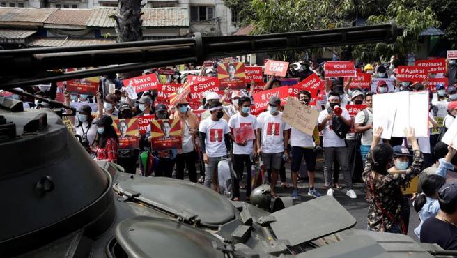Manifestantes protestan en Rangún contra el golpe de estado militar en Birmania (Myanmar), vigilados por soldados y vehículos armados.