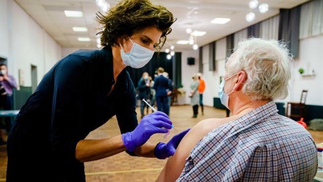 Una enfermera administra la vacuna contra la COVID-19 a una mujer en Holanda.