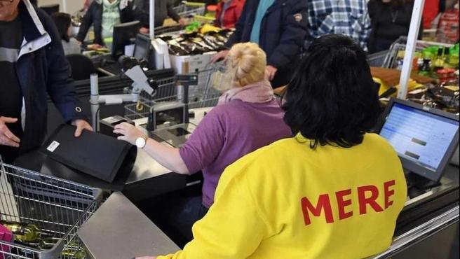 Una trabajadora de un supermercado Mere atiende a los clientes.