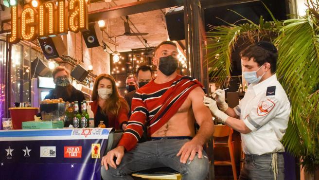 Uno de las jóvenes que recibió la vacuna contra la Covid en un bar israelí en Tel Aviv..