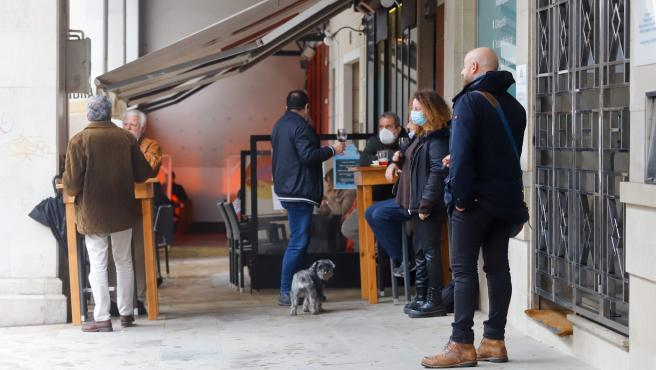 Varias personas en la terraza de un bar un día antes del cierre de la hostelería en Vigo.