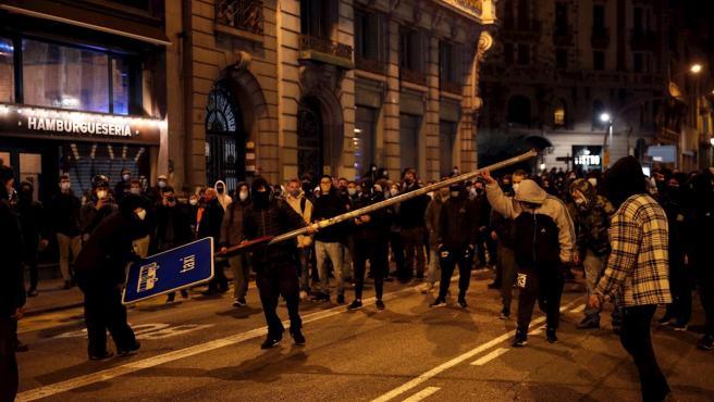 Manifestantes rompen mobiliario urbano en la sexta noche de protestas y disturbios en Barcelona por la libertad de Pablo Hasel.
