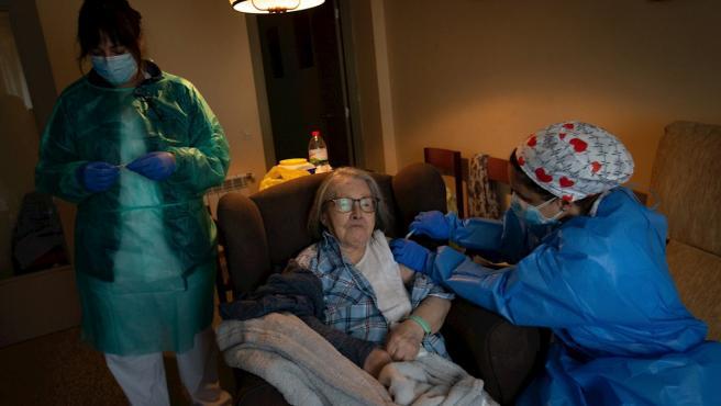 Una enfermera administra la primera dosis de la vacuna BioNTech Pfizer a una paciente mayor de 80 años en su domicilio del barrio del Raval de Barcelona.