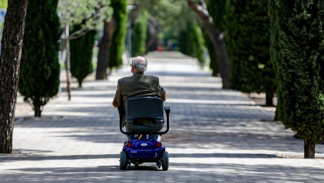 Archivo - Un anciano en silla de ruedas eléctrica en un parque de Madrid